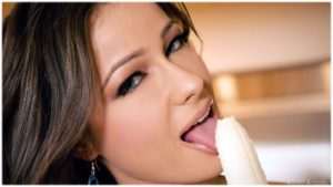 Woman licking banana